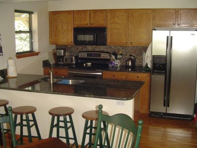 Kitchen adjacent to dining area, large extended table with 6 chairs.