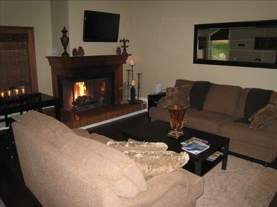 Comfy sofas near the roaring fireplace. Wall mounted HDTV