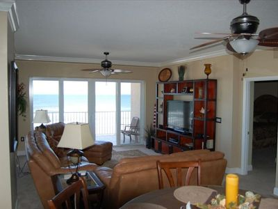 Fully furnished living room has a private balcony with an oceanfront view.