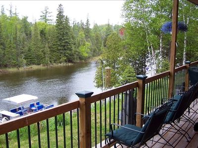 Deck overlooking river with the pontoon boat included in rental.