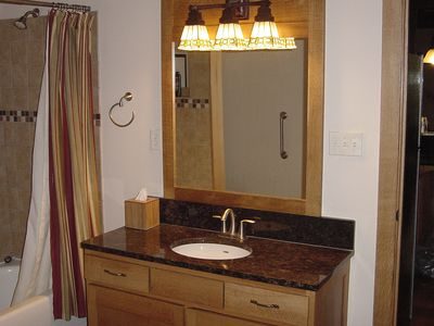 Master bath has granite to match the kitchen and quarter-sawn vanity and mirror