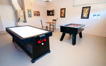 Games room with foosbal, pool table, table tennis, air hockey and darts.