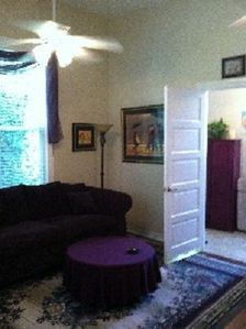 Living room. (eggplant colored sofa) and entrance into the bath.