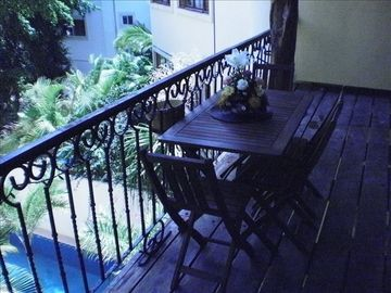 Balcony off of living area overlooking pool and garden