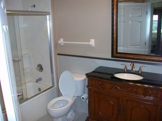 Newly renovated guest bath room with marble walls and granite counter top. - Daytona Beach condo vacation rental photo