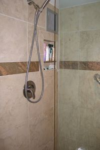 Custom travertine shower with granite appointments and toiletry niche