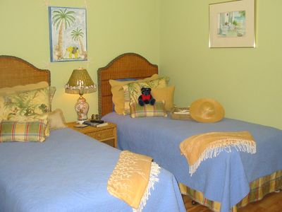 Comfortable, colorful, guest bedroom with two twin beds and private bath.