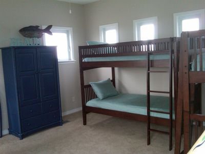 Third floor loft with two sets of bunk beds, wardrobe, entertainment area.