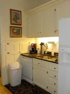 Behind main kitchen, a service kitchen w/extra sink, dishwasher, fridge, storage