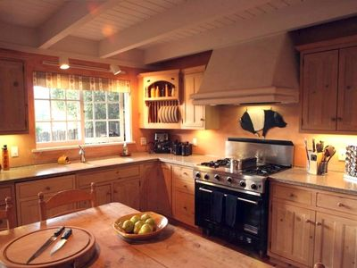 Corner of Chef's kitchen with Viking range and kitchen table for 8