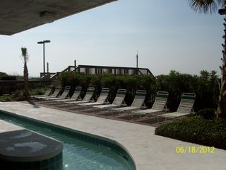 Cherry Grove Beach condo photo - sundeck and chairs at the lazy river with walkway to the beach in the background