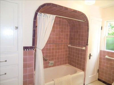 Upstairs bath with beautiful original tiles featuring bath/shower