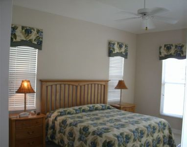 Master Bedroom with private bath, walk in closet and view to pool/lanai area.