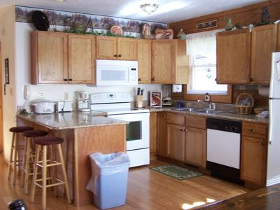 Kitchen with granite counter tops, glass top stove, microwave, and appliances