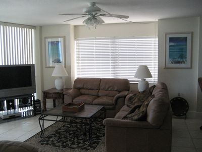"Spacious living room with leather furniture and 42"" TV."