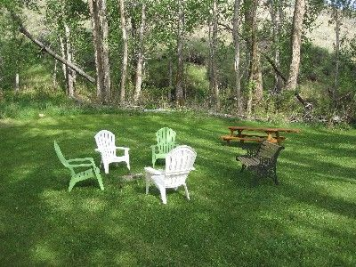 Gardiner cabin rental - back yard, fire pit, plenty of wood. picnic table. Small stream near for water.