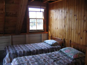 Second bedroom with twin beds, a double bed and an armoire.