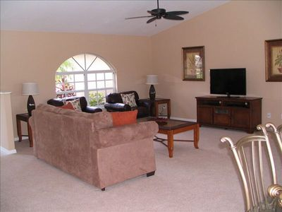 Spacious living room with TV, sleeper sofa, two leather chairs and tables.