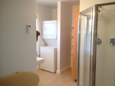 Guest Bathroom with Stall Shower and stackable Laundry Machine