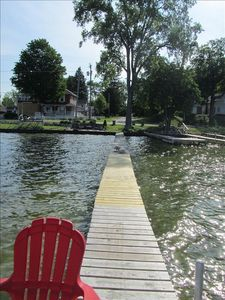 private dock looking back at shore from platform with two chairs and table