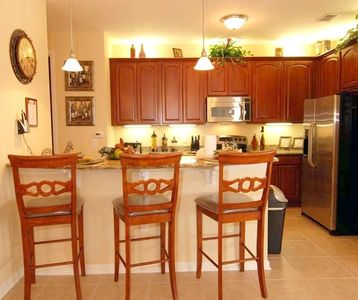 Contemporary kitchen with 3 stools, granite counters, & stainless appliances