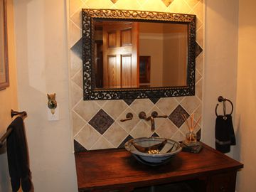 Guest bath with custom tile work and vessel sink