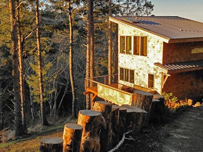 Neskowin cabin rental - Coming into the driveway with the log-lined retaining wall and winter sunrise.