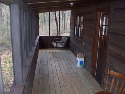 Screened in porch on the front of the cabin.