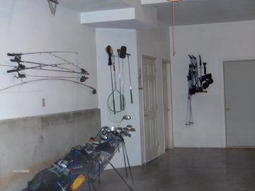 garage area with fishing poles and sets of golf clubs