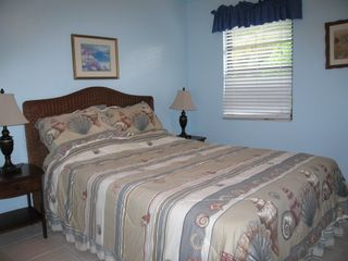 King Bedroom offers tropical garden views, paddle fan, A/C. - Spanish Wells villa vacation rental photo