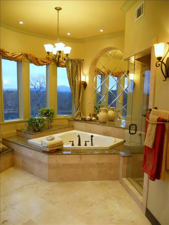 Master bathroom jetted tub and shower to right with lake view.