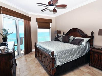 "King size master bedroom with 47"" flatscreen and door to balcony"