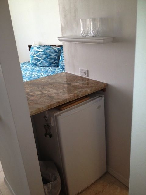 Kitchenette counter and small refrigerator.