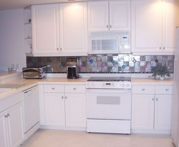 designer tile backsplash in fully equipped kitchen