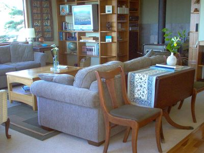 Living room is cozy & comfy, has a wood stove, loads of books, and views!
