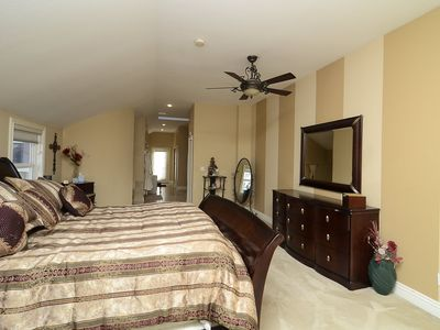 Large area with extra deep king bed and large open floor area before bath.