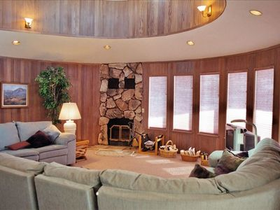 Circular Living room with wood burning fireplace--Redwood paneling.