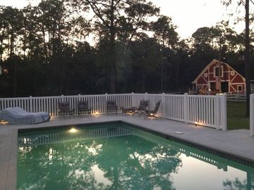 pool at dusk with automatic perimeter lights and horse barn/stable in background