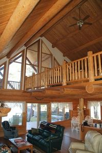 Looking from the stairs to the great room, loft, deck and the river