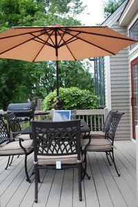 Sunny deck with comfortable dining seats for six and barbeque grill.