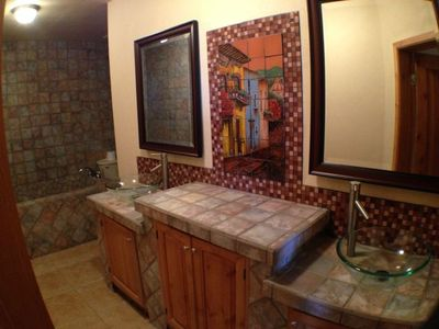 Bathroom 3 is Oversized with 2 sinks, toilet and large tile tub and shower.