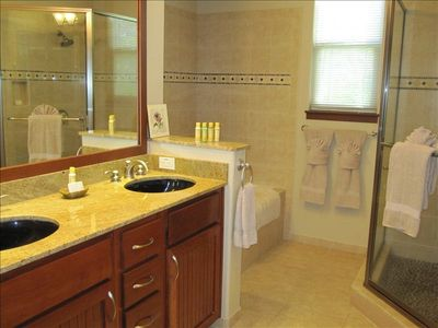 Master Bathroom with double sink, large bath tub and shower with rock flooring