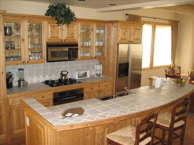 Open kitchen with top grade appliances.. large bar for visiting with the cook..