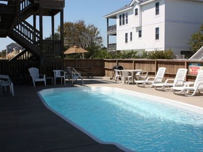 Pool area w/ lots of chairs, charcoal grill, picnic table, gated access to decks