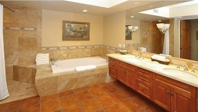 Travertine-tiled, spa bathrooms grace both Grand-Master bedroom suites.