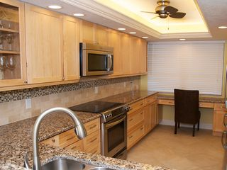 Redington Shores condo photo - Spacious kitchen with desk area, stainless appliances, and granite counters.