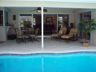 Lanai with grill, table/chairs, lounge chairs, fan, surround sound/music, pool