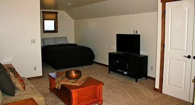 Queen bed and sofa and TV in guest suite above triple car garage.
