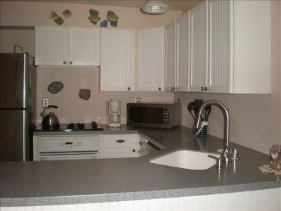 Kitchen features a Corian countertop, many small appliances