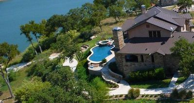 Aerial view of home, pool, hot tub and golf cart path to the boat dock